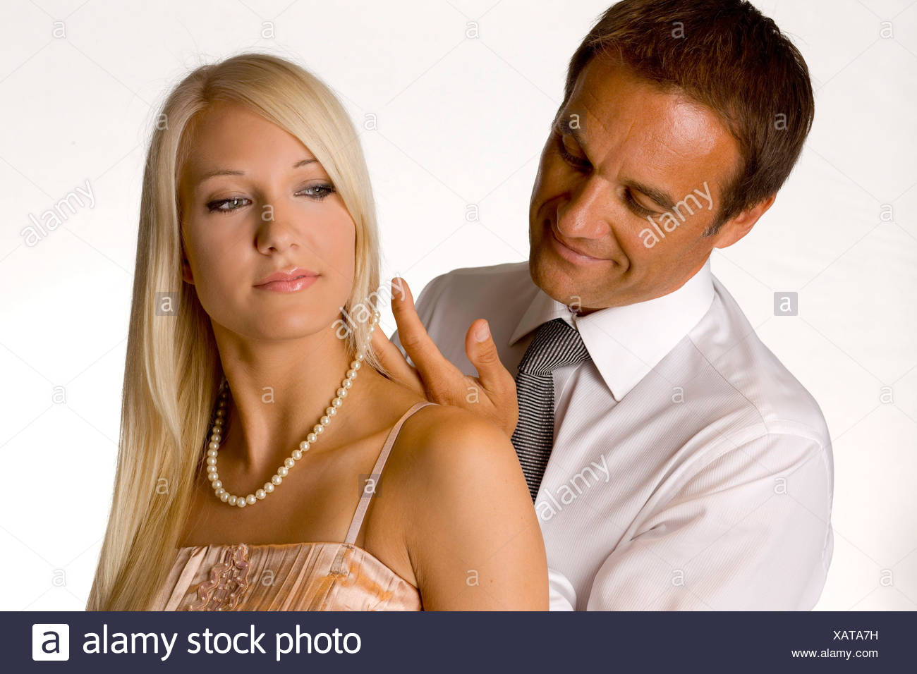 older man putting on a necklace to his younger girlfriend - Stock Image