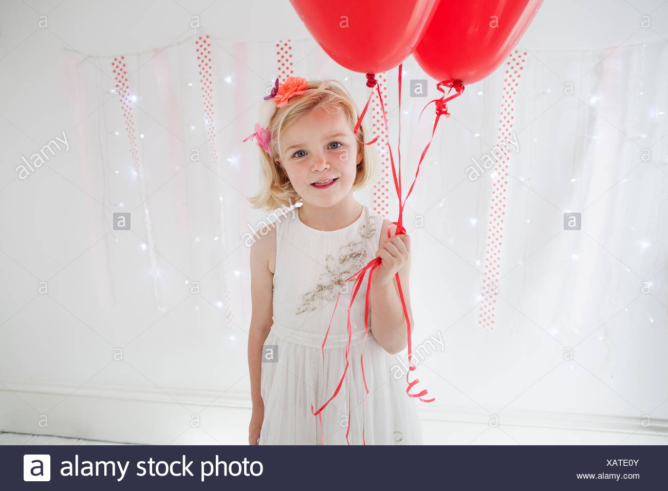 Young girl posing for a picture in a photographers studio, holding red balloons. - Stock Image
