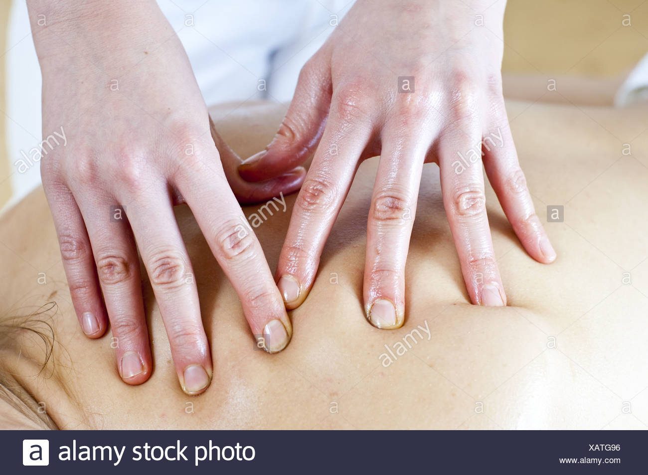 hands giving a massage to a back (model-released) - Stock Image