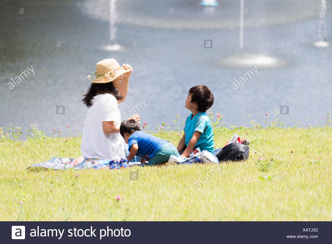Woman With Her Sons Sitting On Field By Lake - Stock Image
