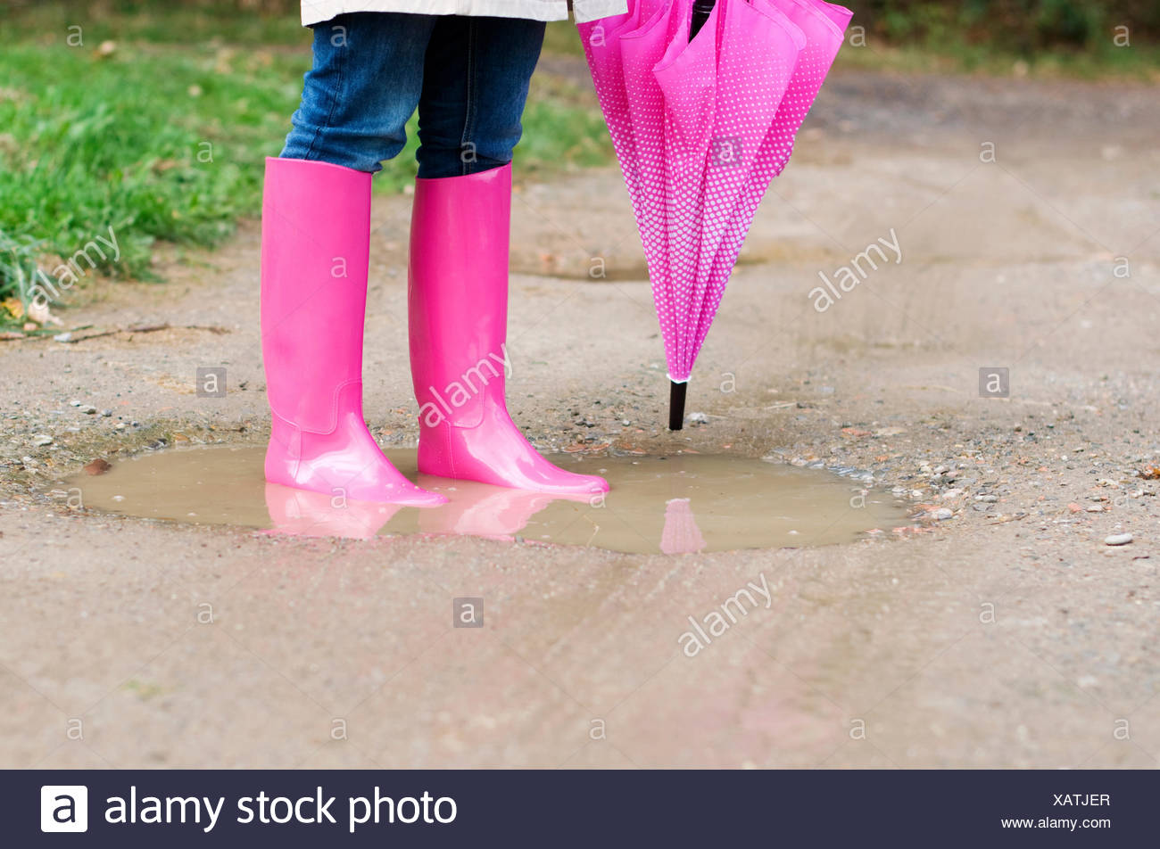 Young woman standing in puddle, Debica, Poland. - Stock Image