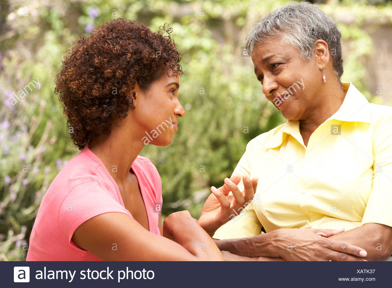 Senior Woman Being Consoled By Adult Daughter - Stock Image