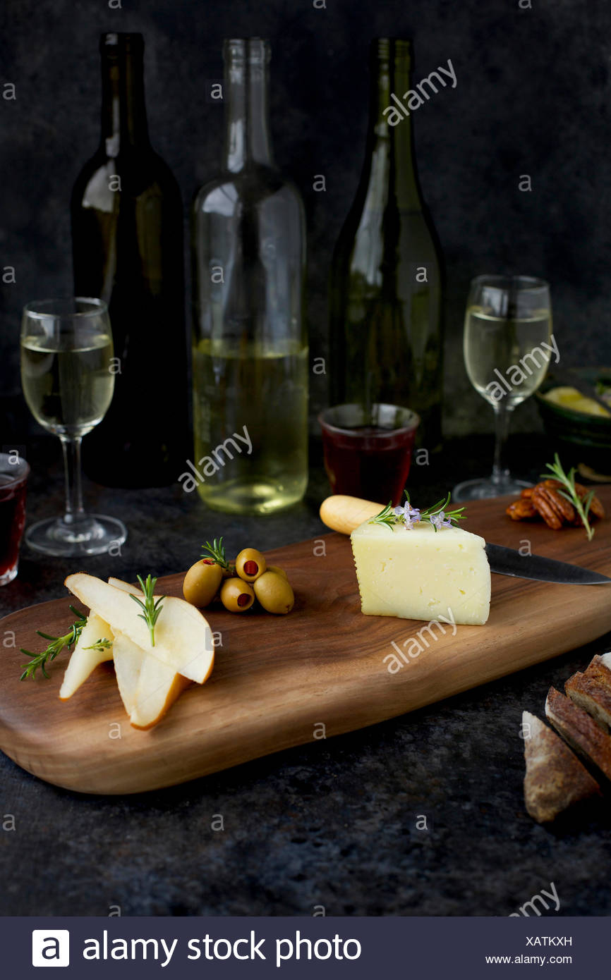 Fromage Fort Cheese Spread served with French bread, spicy pecans, quince jam, Manchego, olives, pears and an assortment of wine. Photographed on blac - Stock Image