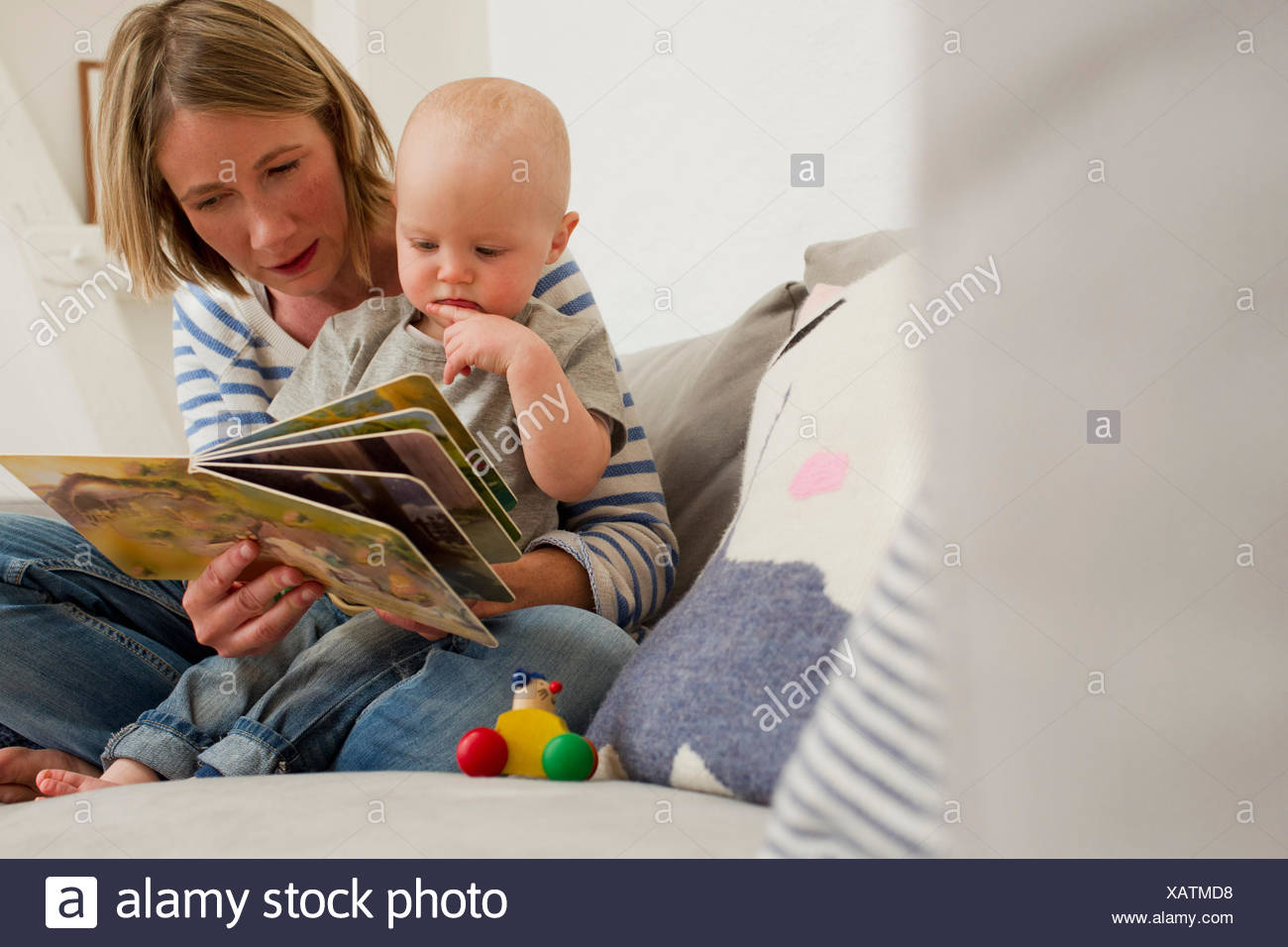 Mature mother and baby daughter on sitting room sofa reading storybook - Stock Image