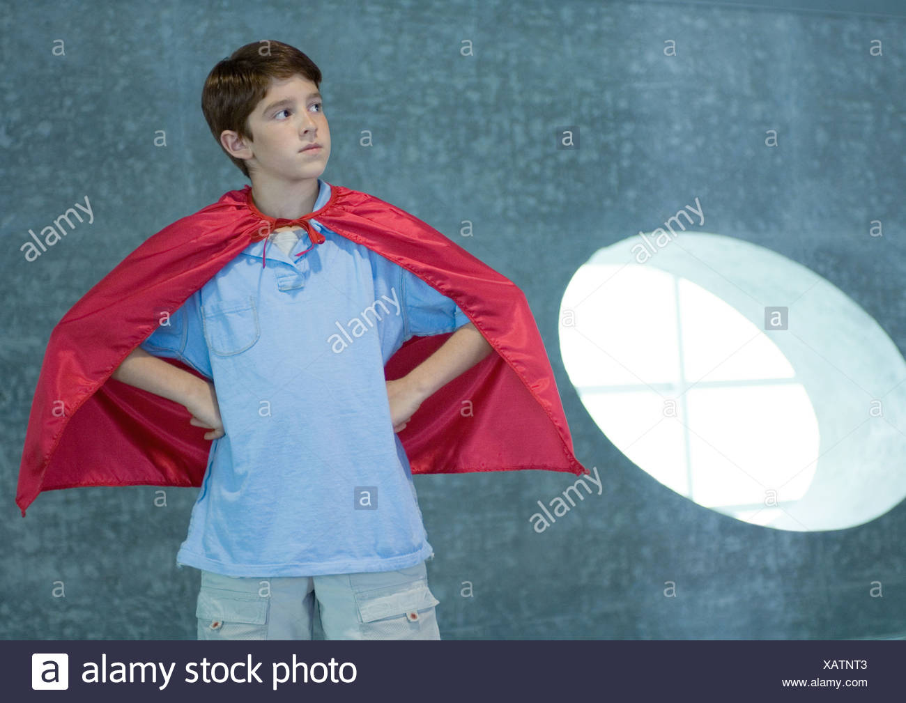 Boy wearing red cape, hands on hips - Stock Image