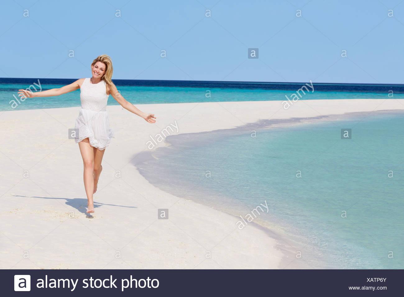 Woman Running On Beautiful Tropical Beach - Stock Image