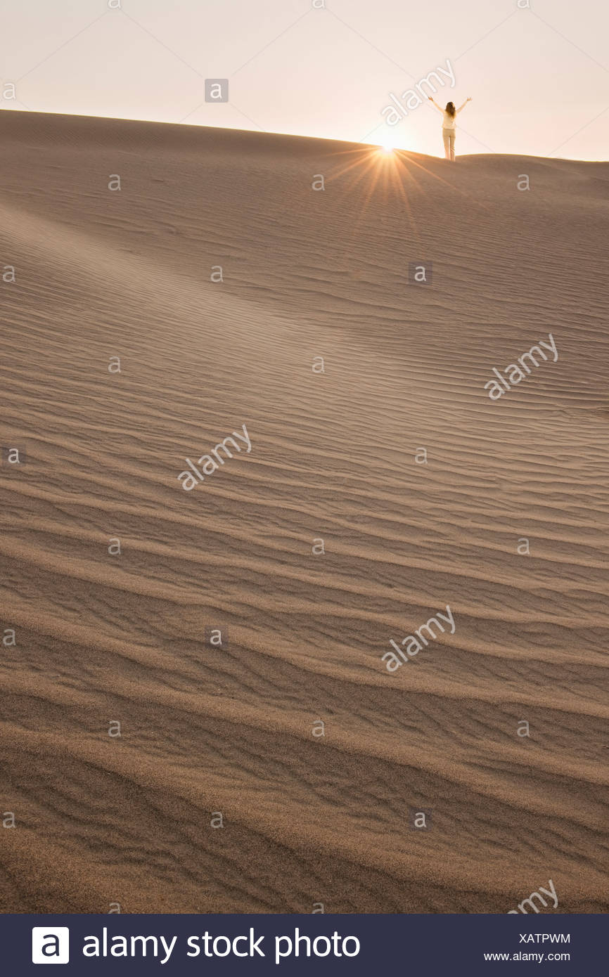 Woman with arms up, standing in desert - Stock Image