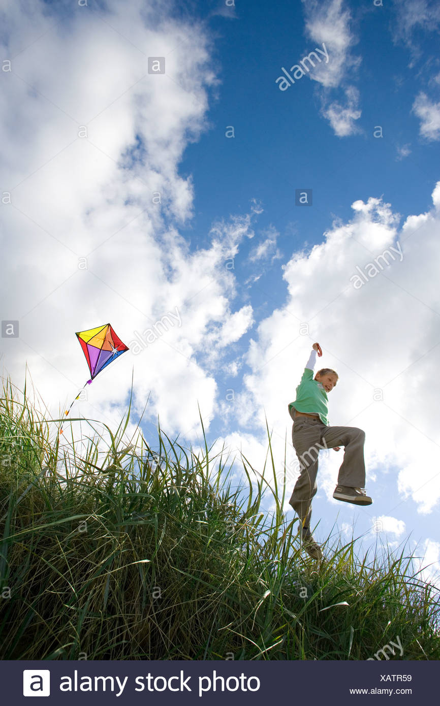 Boy 7-9 years flying kite outdoors, low angle view - Stock Image