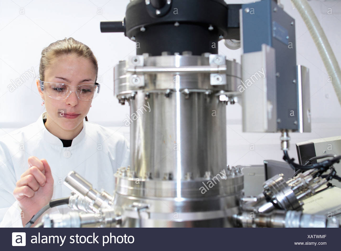 Female lab technician operating scientific equipment - Stock Image