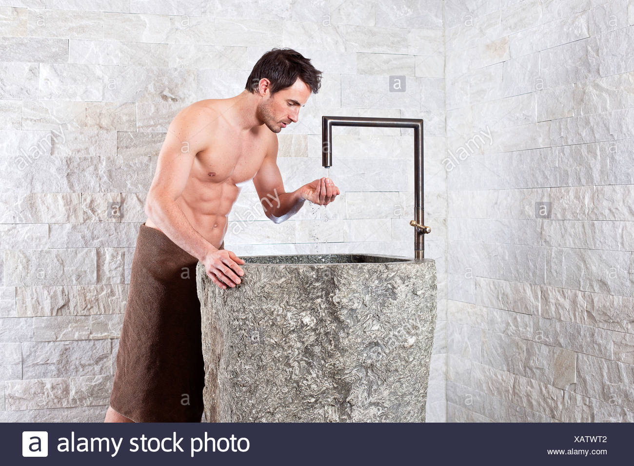 Bare-chested man standing at a water fountain in a spa complex - Stock Image