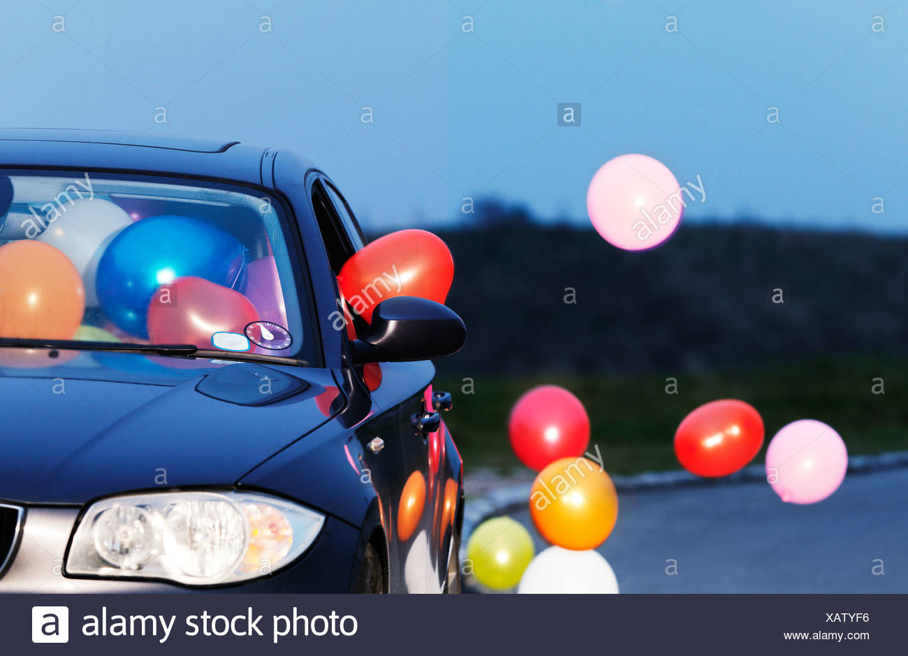 Colorful balloons coming out car window - Stock Image