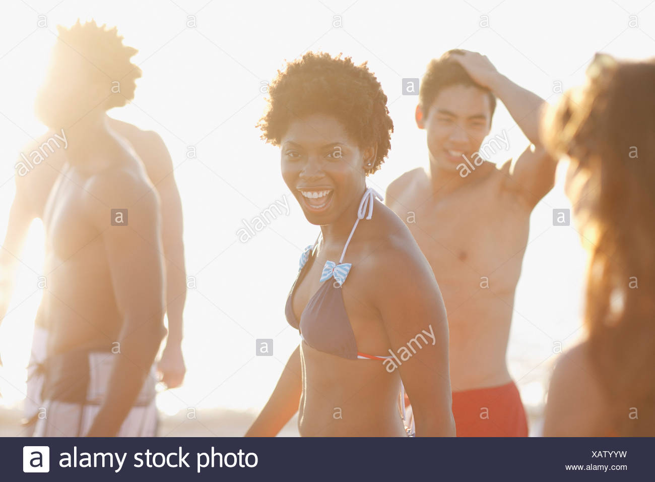 Friends in swimsuits walking on beach - Stock Image