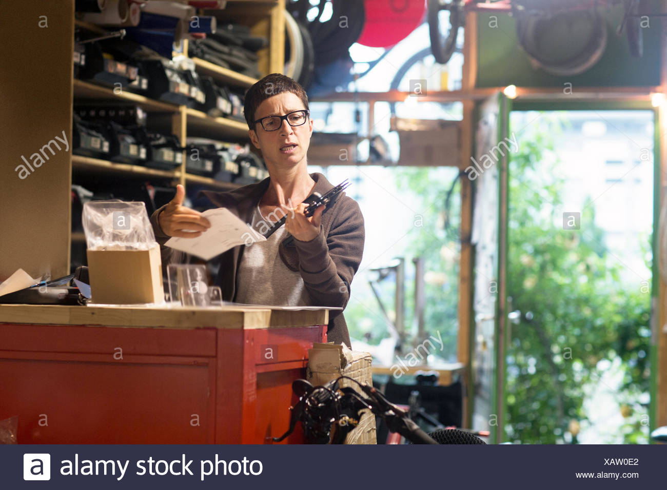 Woman at counter in bicycle workshop holding bike part and paperwork - Stock Image