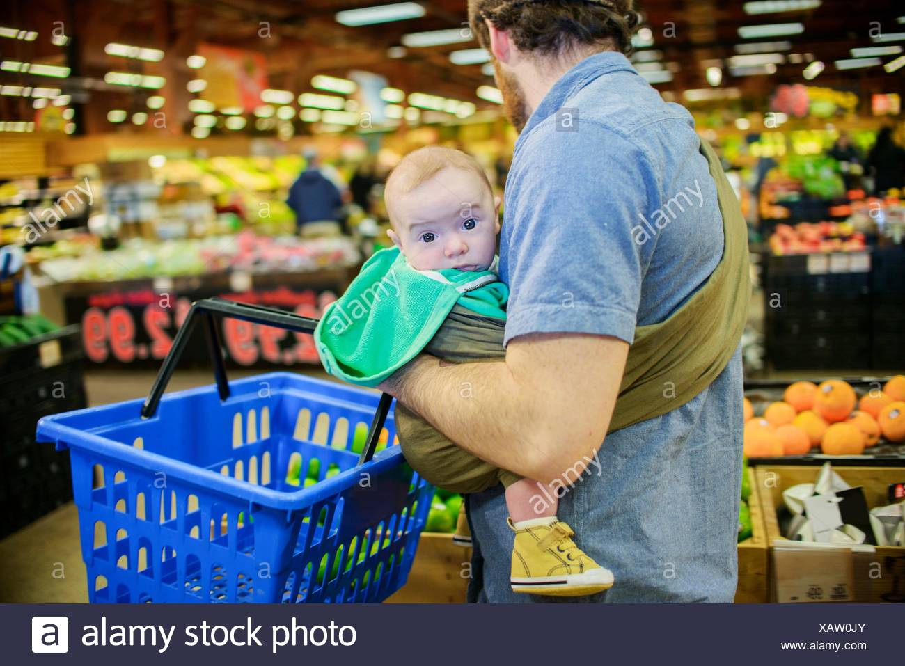 Father holding baby son and shopping basket in supermarket - Stock Image