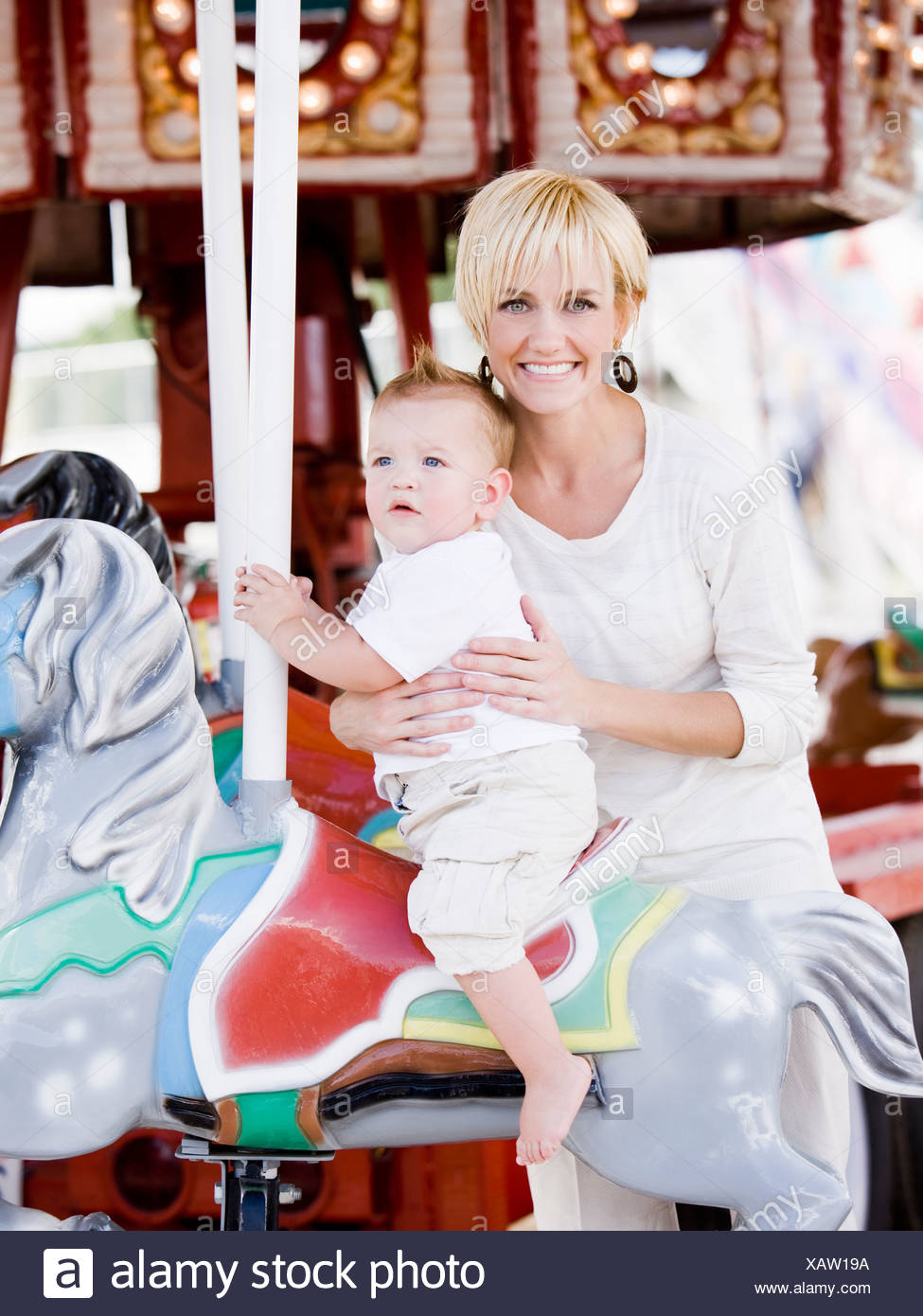 mother and baby on a merry-go-round - Stock Image