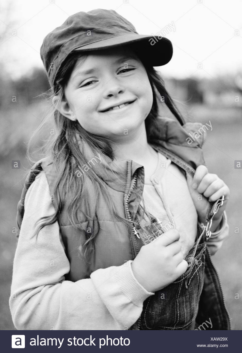 Portrait of a girl with a cap and dungarees, Sweden. - Stock Image