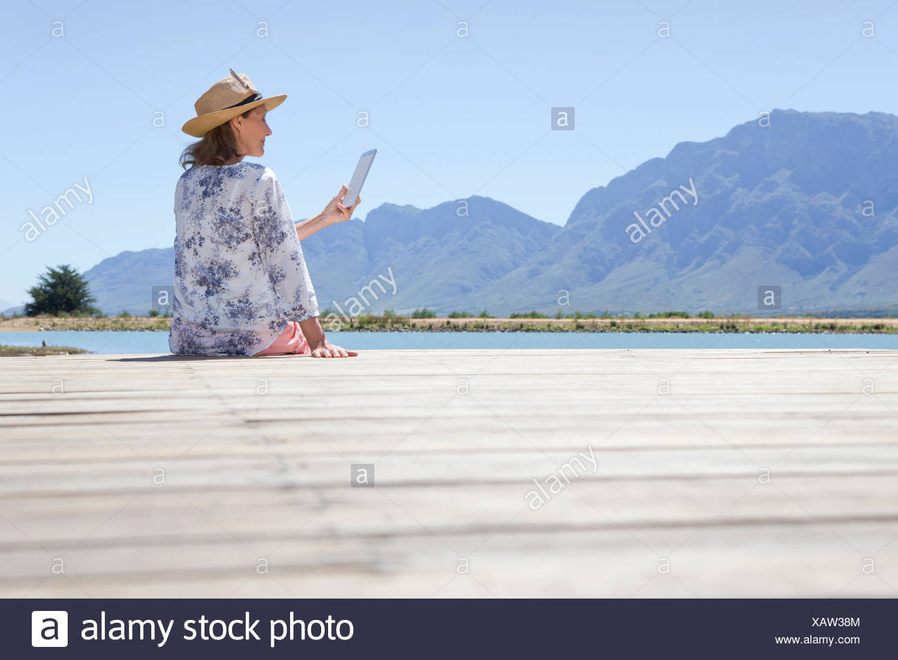 Senior woman sitting on jetty with digital tablet - Stock Image
