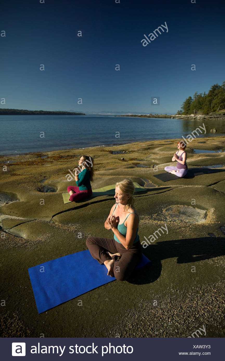 Yogpractioners relax meditate early morning sun - Stock Image