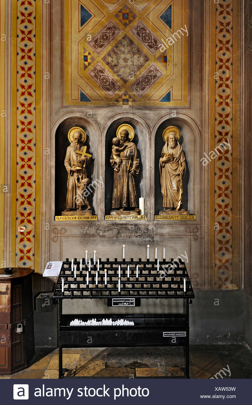 Ludwigskirche, St. Louis Church, three statues of saints and candles emitting little soot, Munich, Bavaria, Germany, Europe - Stock Image