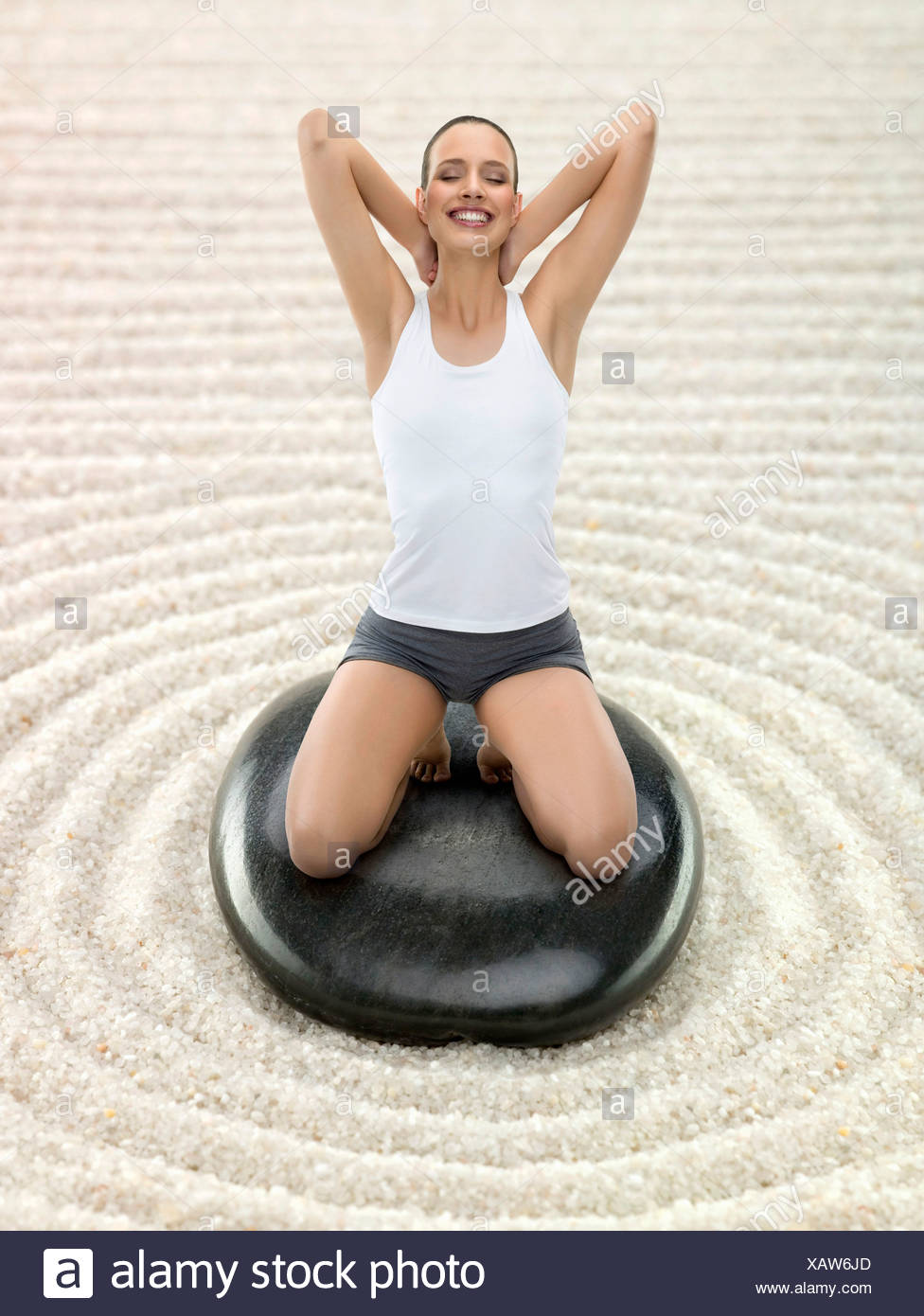 Portrait young adult woman meditating Zen garden, digital composite - Stock Image