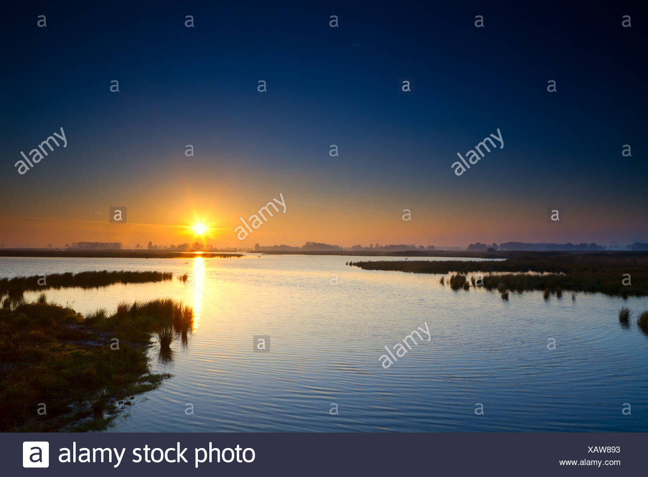 sun rising up over blue lake Stock Photo