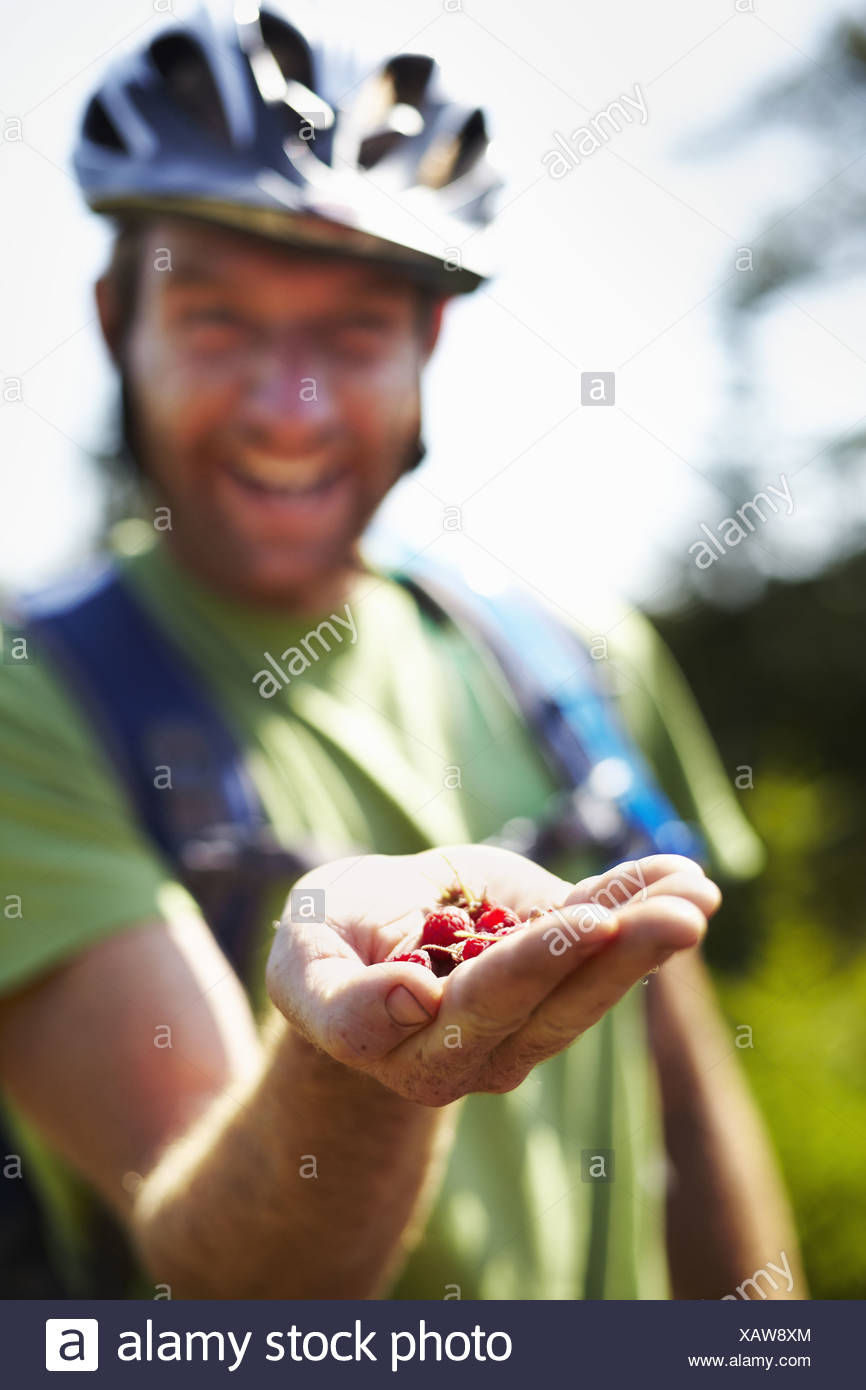 Hiker on Trail with Native Raspberries - Stock Image