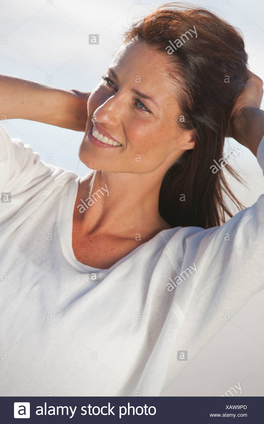 Close up of smiling woman with hands in hair - Stock Image