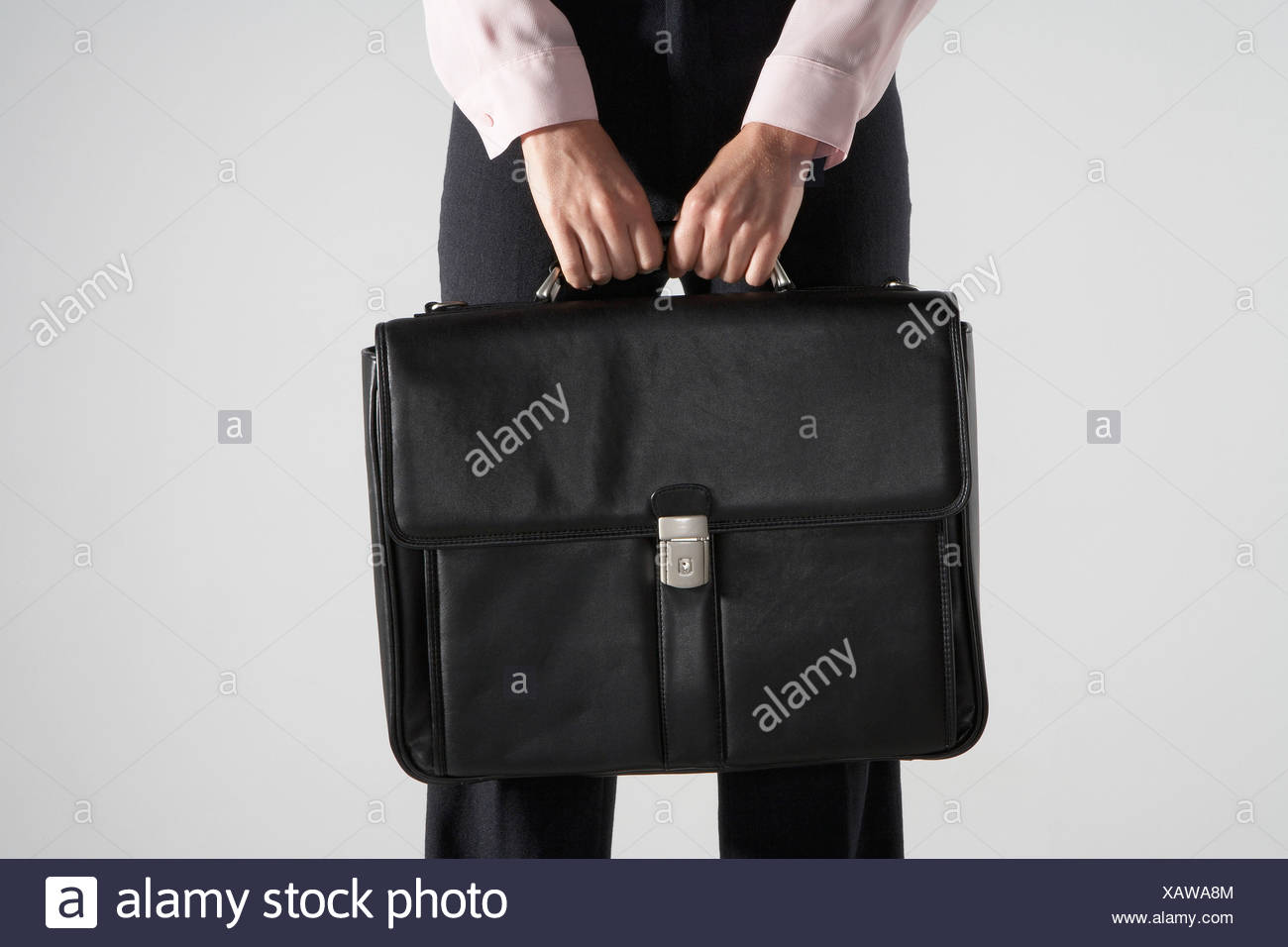 Woman holding a black brief case against her. - Stock Image