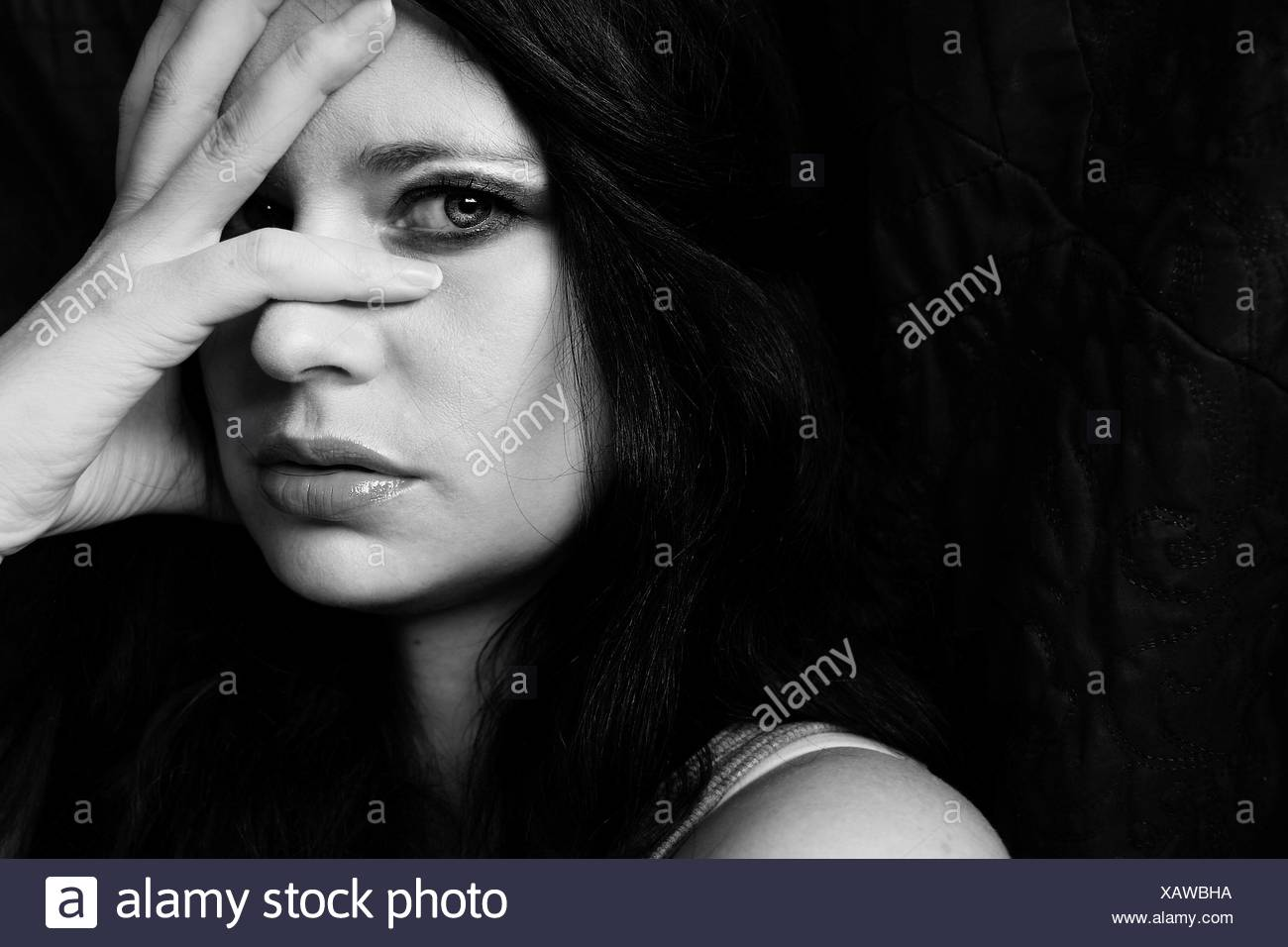 Close-Up Portrait Of Thoughtful Young Woman With Hand On Face Against Black Background - Stock Image