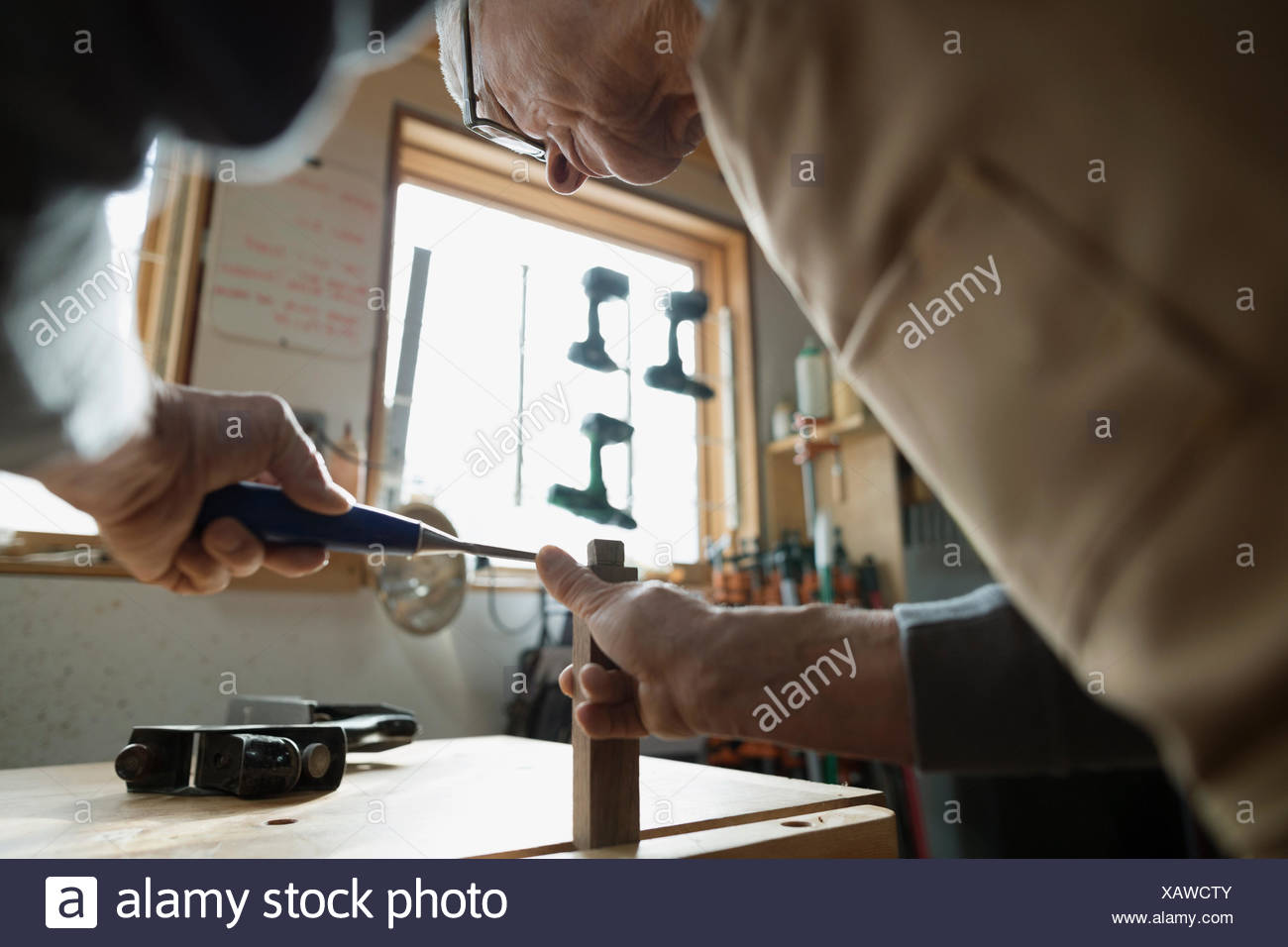Carpenter using chisel on wood block in workshop - Stock Image