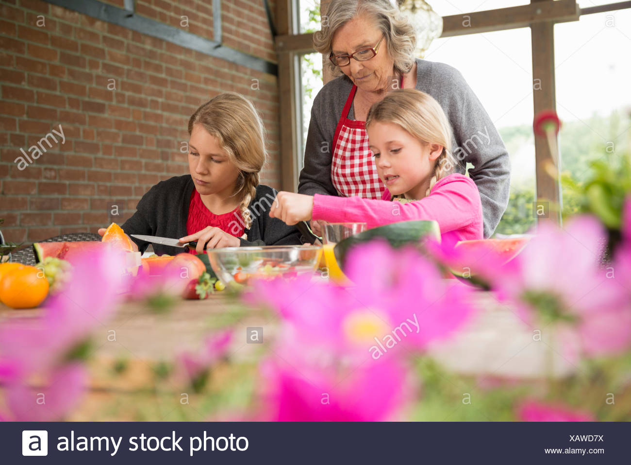 Two sisters and grandmother at kitchen table learning to slice fresh fruit - Stock Image