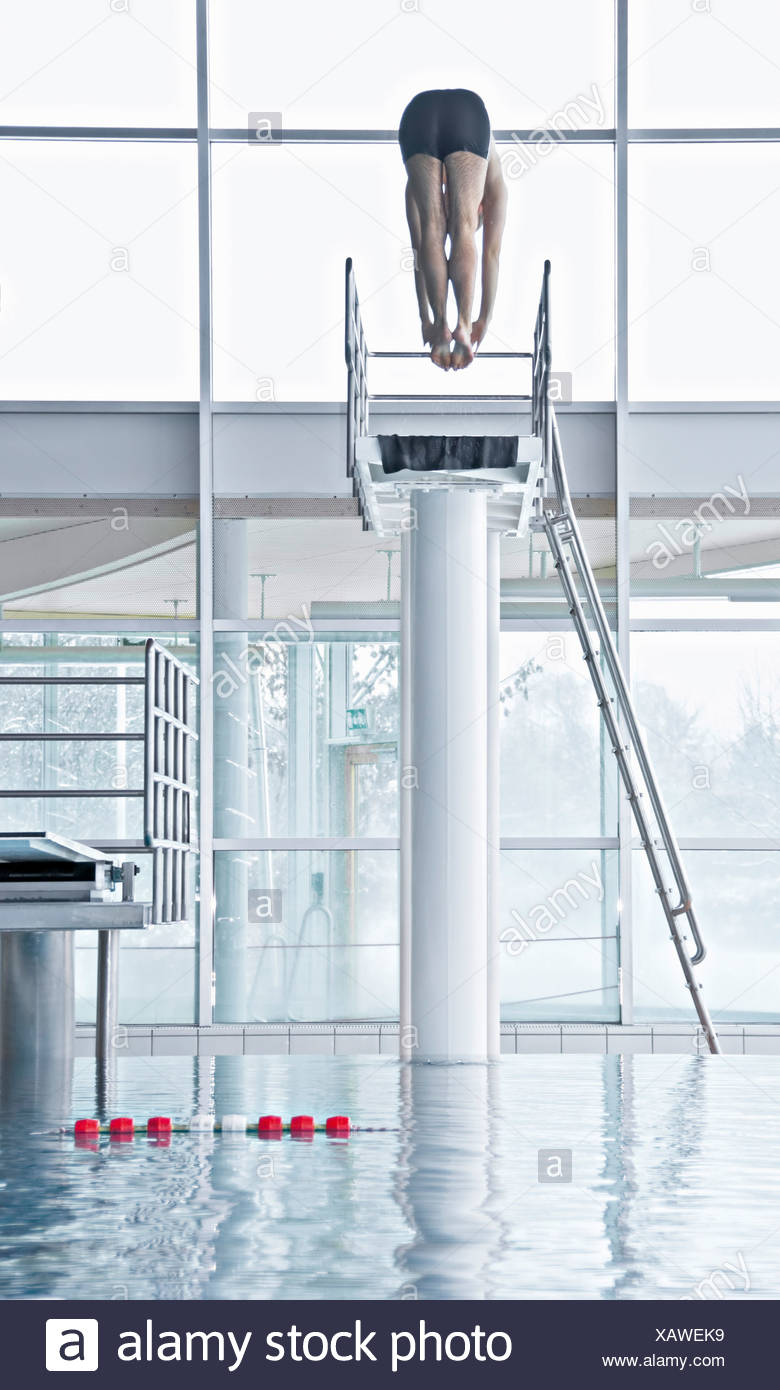 Man jumping from a highboard in an indoor swimming pool - Stock Image