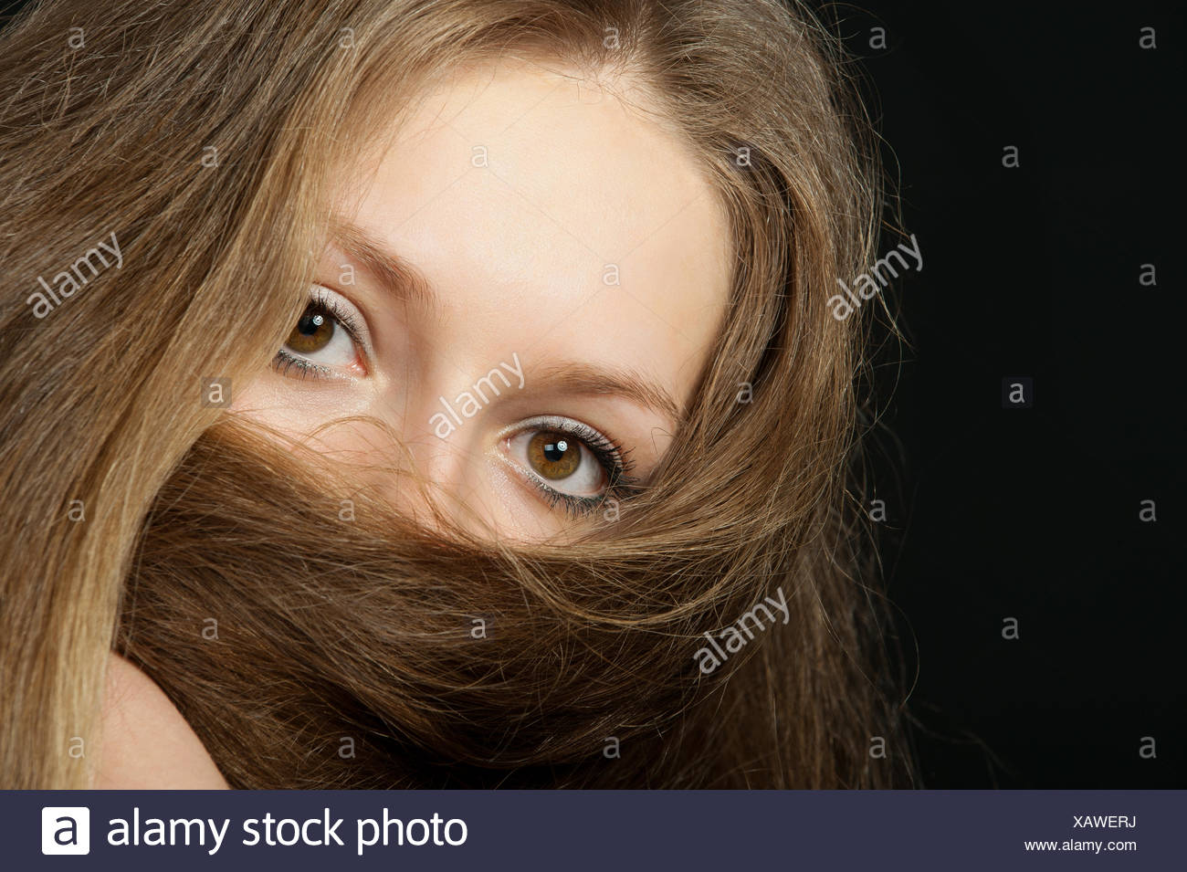 The girl closes long hair the bottom part of the person. A yashmak. - Stock Image