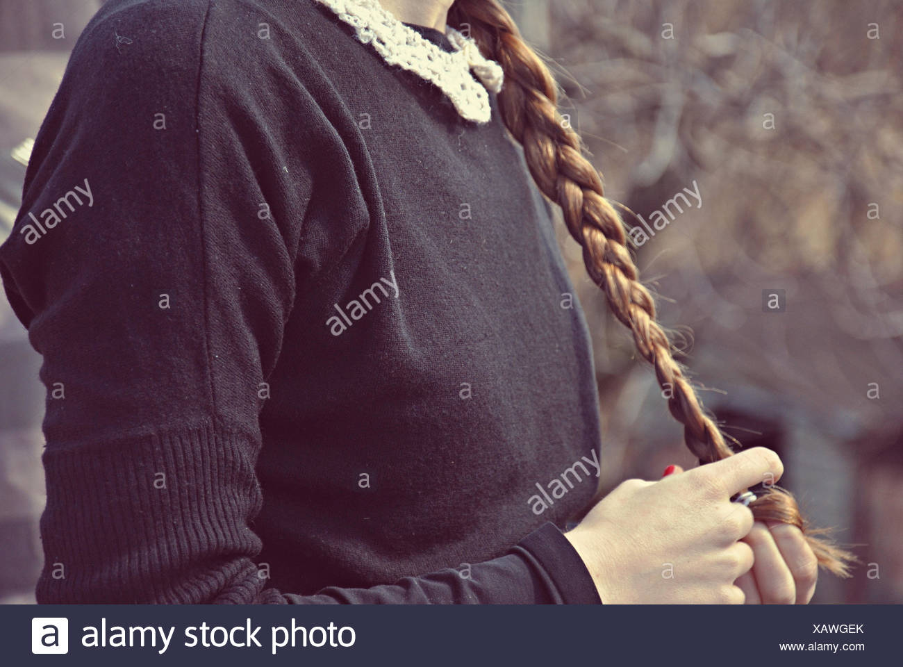 Girl playing with her braid - Stock Image