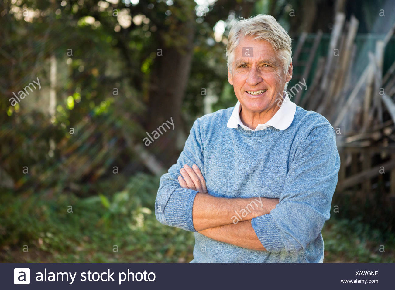 Portrait of confident gardener with arms crossed at garden - Stock Image