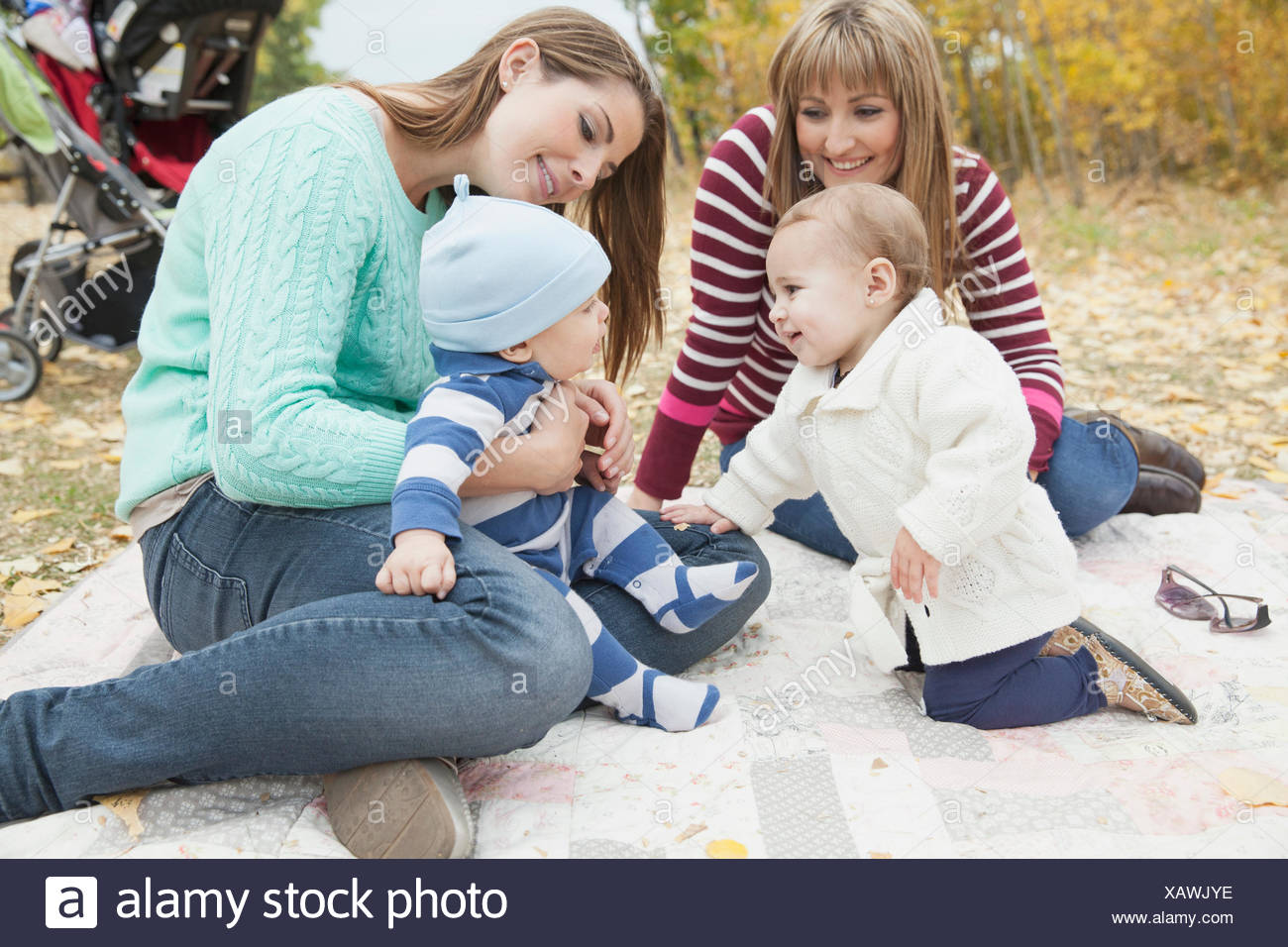 Happy mothers with babies relaxing at park - Stock Image