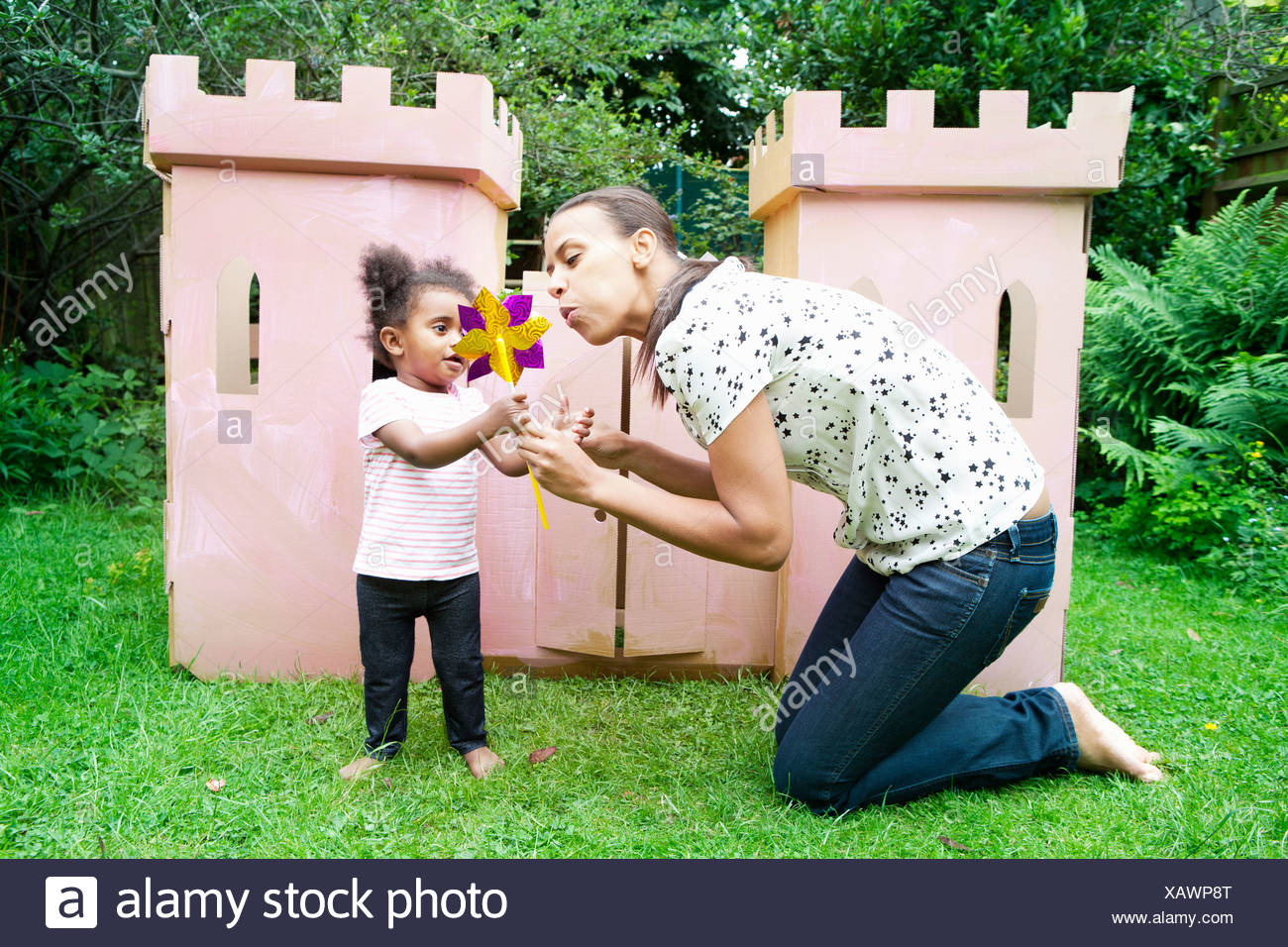 Mother and daughter blowing pinwheel - Stock Image