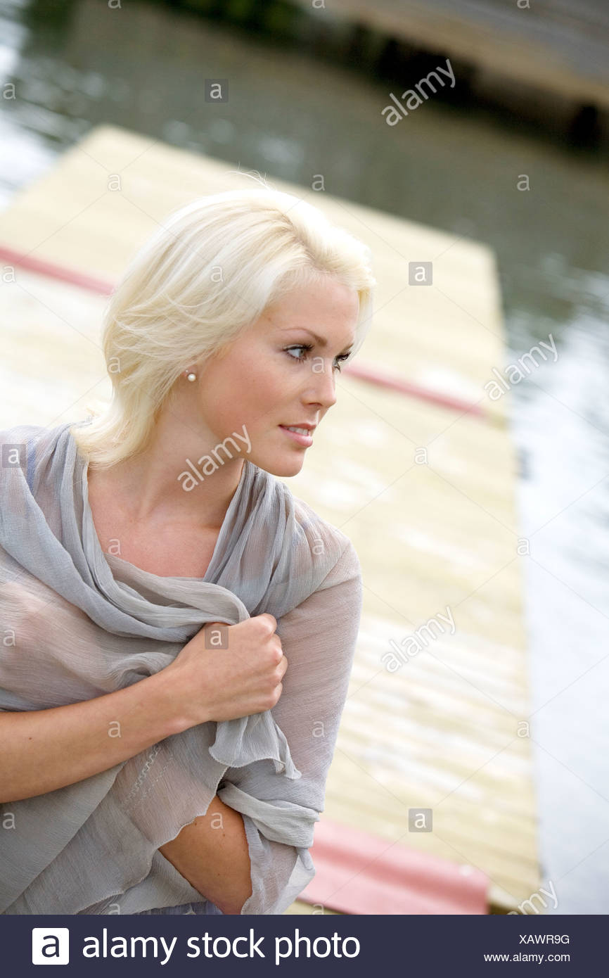 A woman with a scarf sitting on a jetty, Sweden. - Stock Image