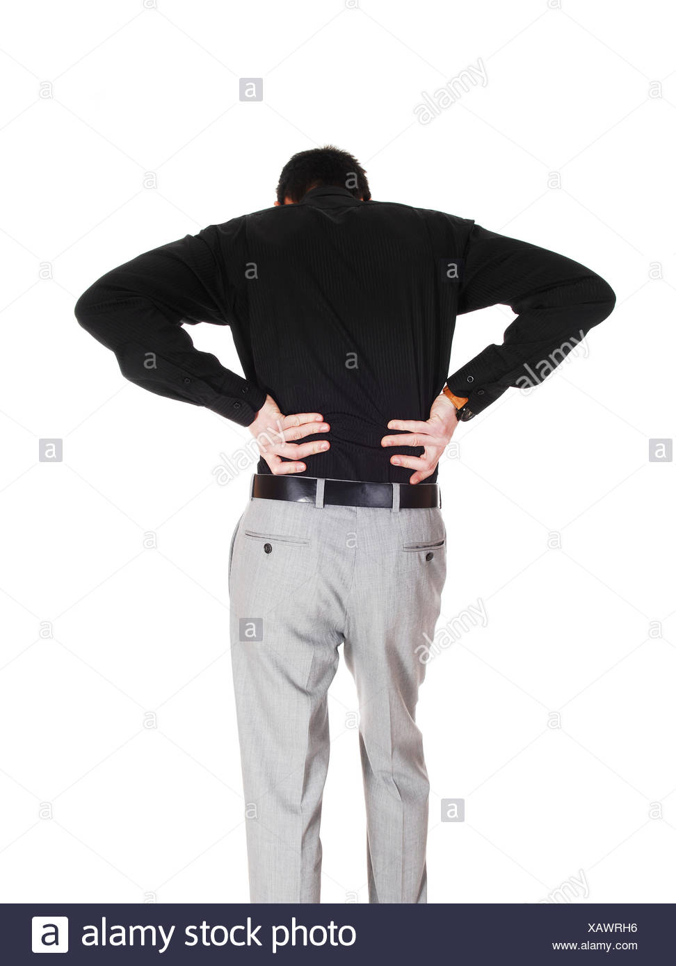 A young businessman standing from the back holding his hands on his back for heavy back pain, isolated for white background. - Stock Image