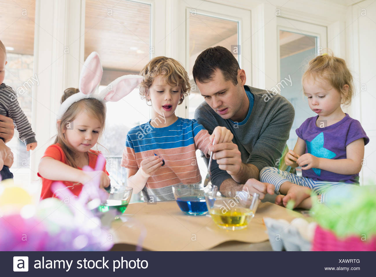 Family dipping Easter eggs in food coloring - Stock Image