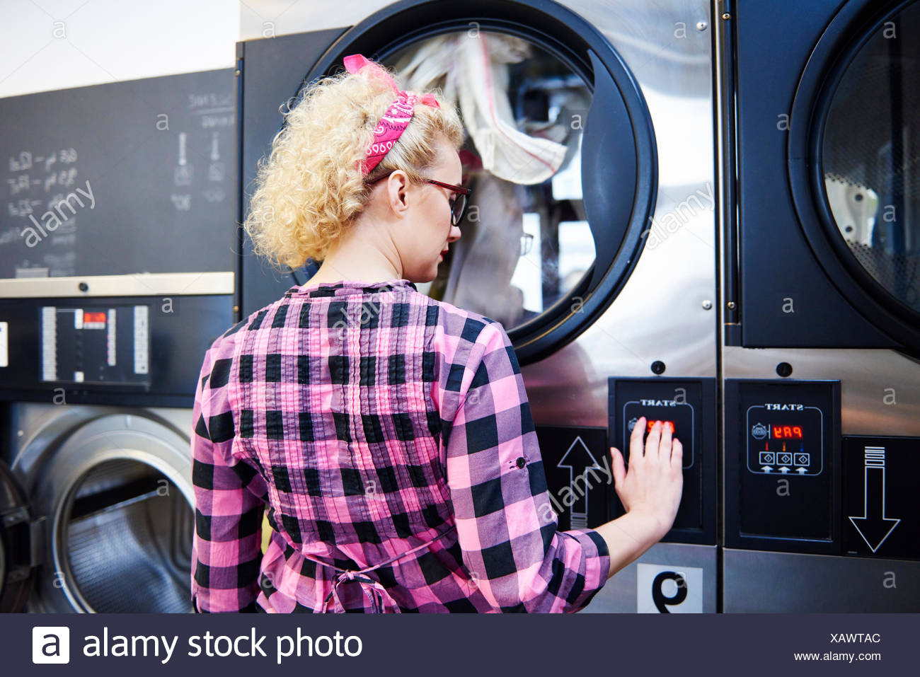 Woman pressing washing machine buttons at laundrette - Stock Image