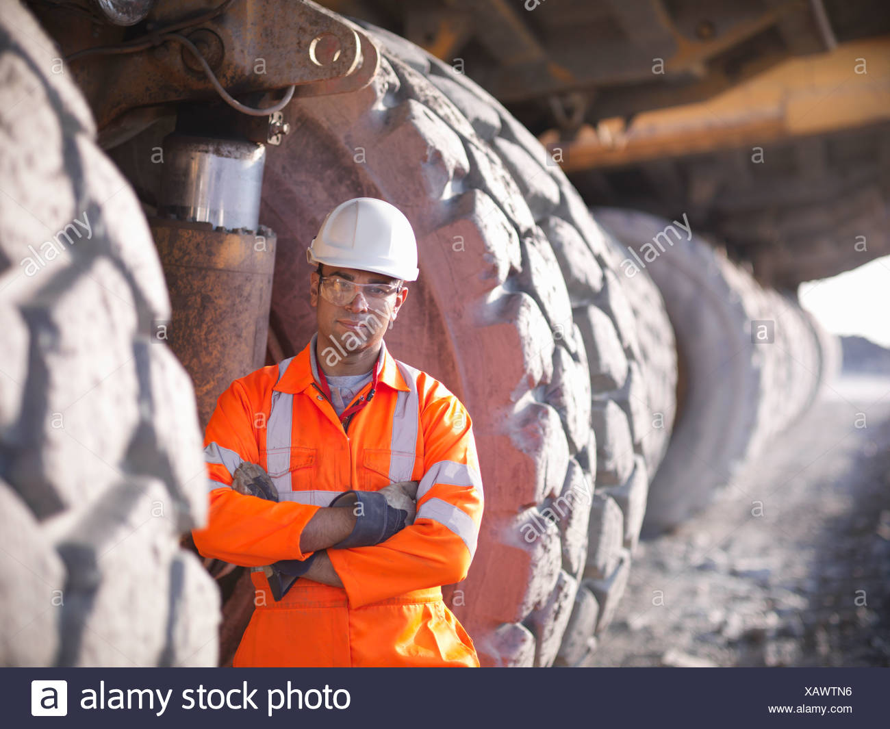 Worker standing by trucks in coal mine - Stock Image