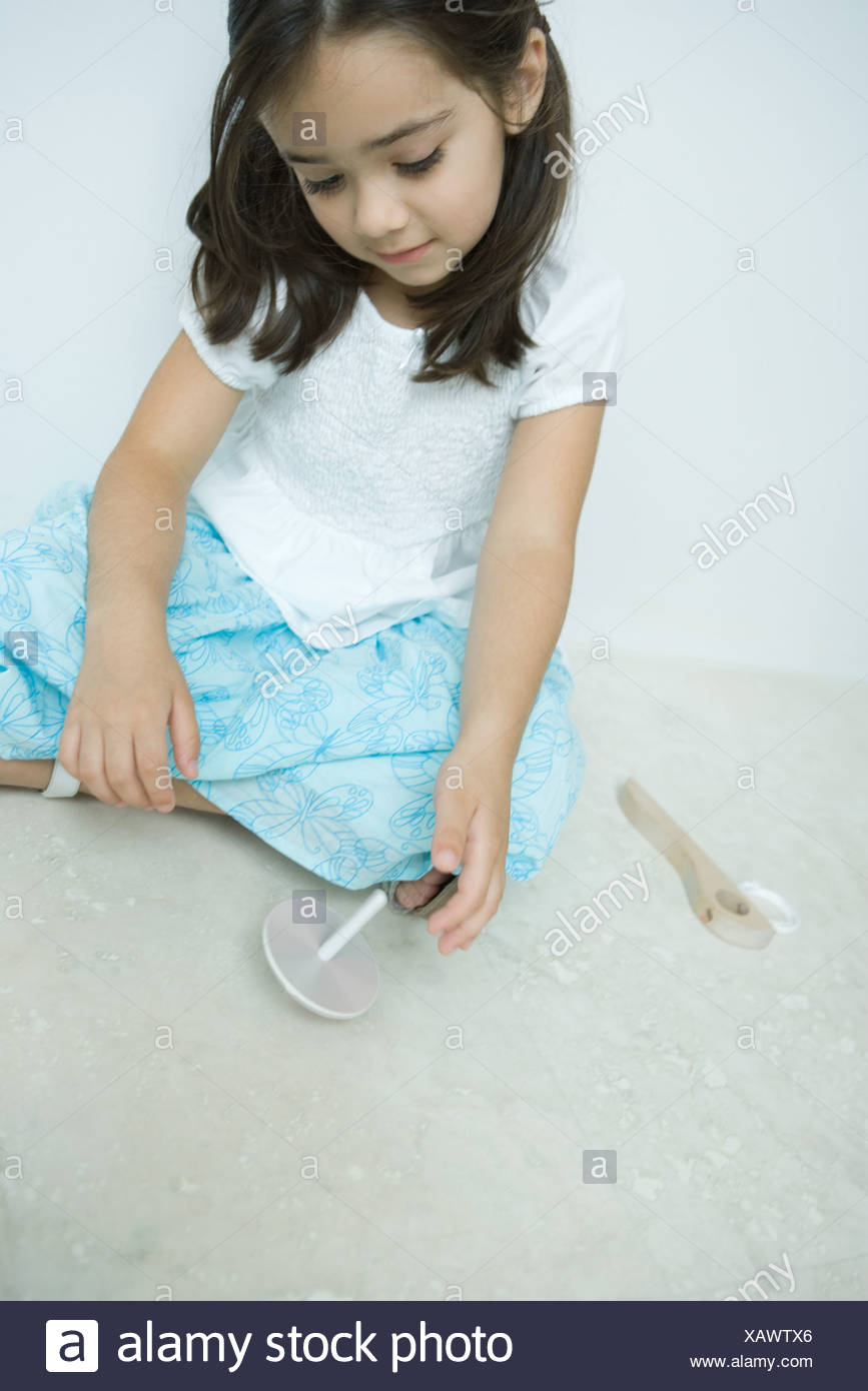 Girl sitting on the ground playing with top, close-up Stock Photo
