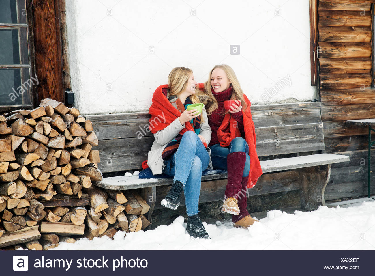 Two young female friends drinking coffee outside wooden cabin - Stock Image