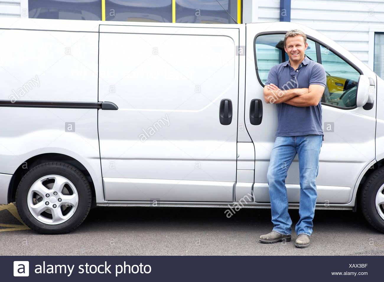 Man standing next to van - Stock Image