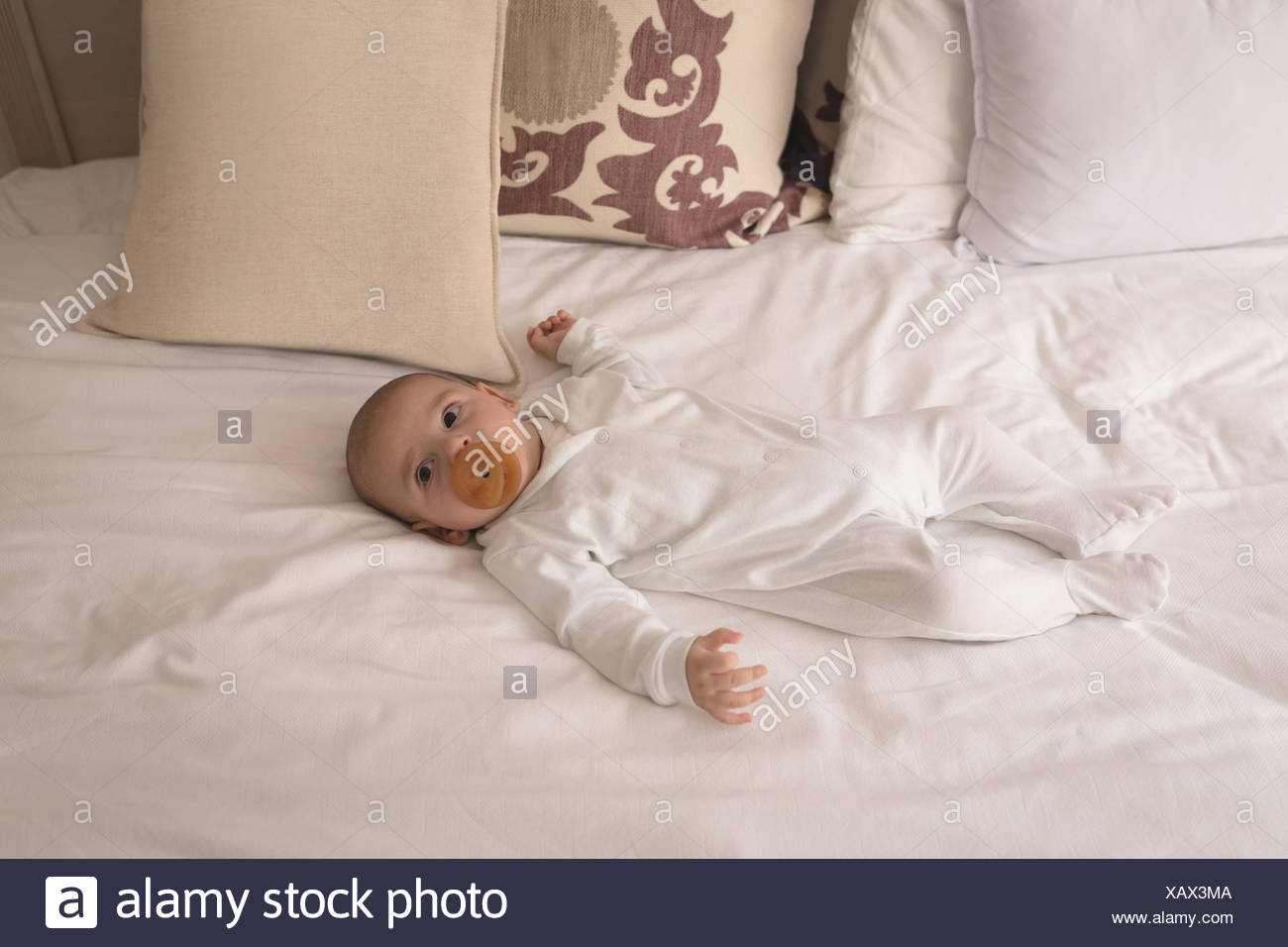 Cute little baby with pacifier in mouth sleeping on bed Stock Photo