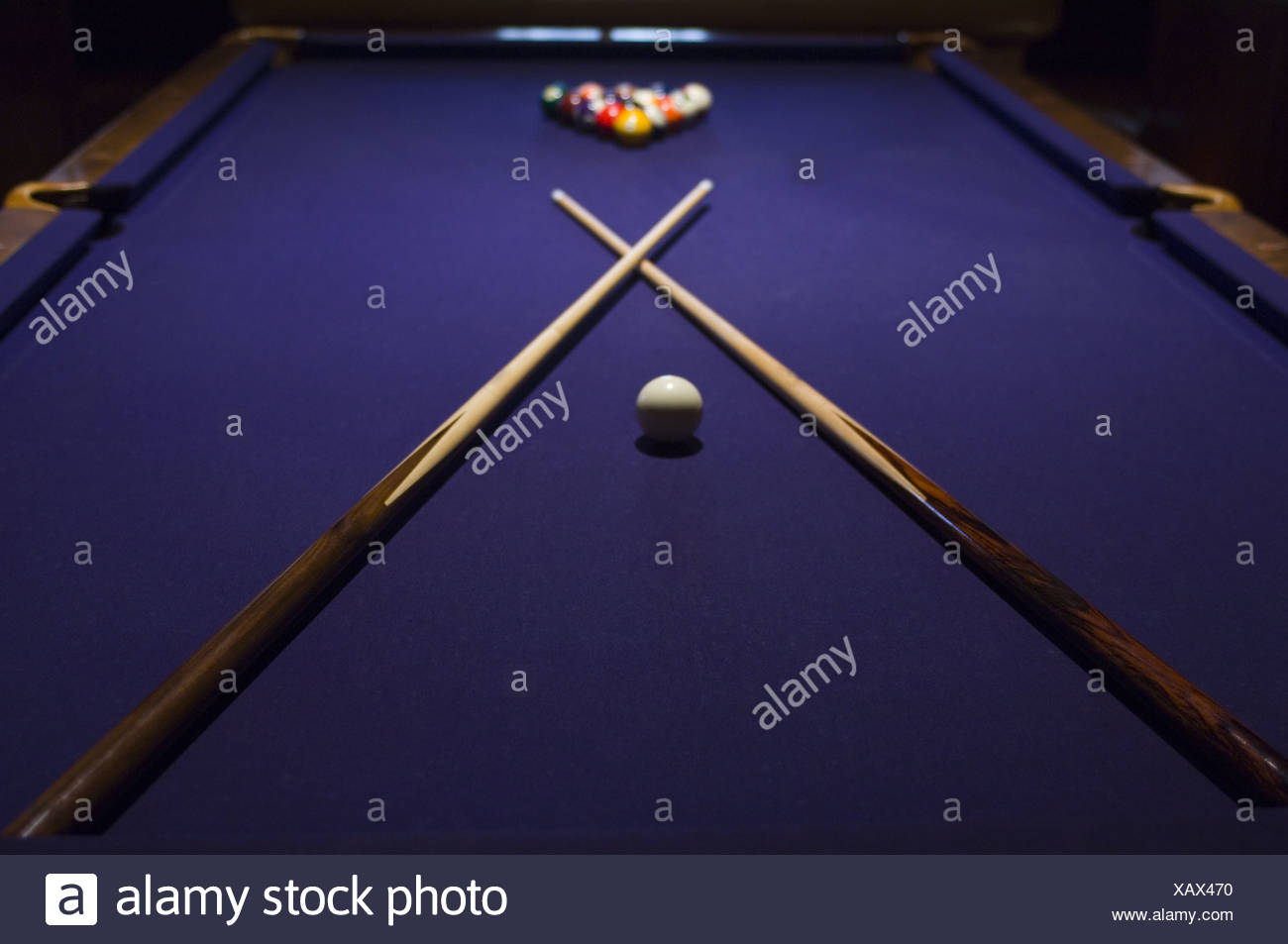 Close-up of pool sticks crossed over on a pool table - Stock Image