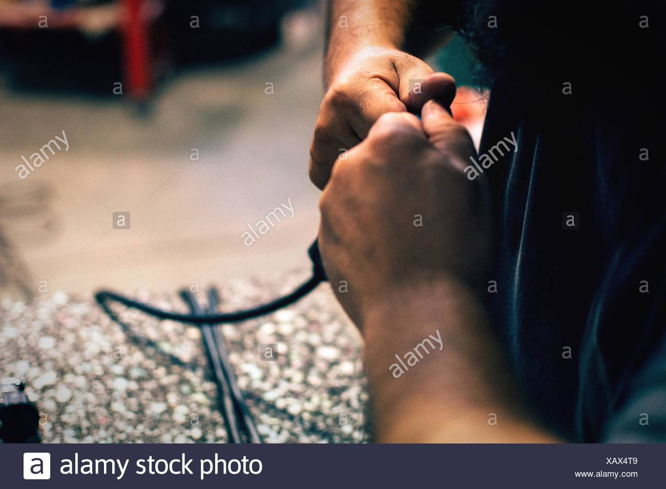 Cropped Hand Of Man Mending Wire Stock Photo
