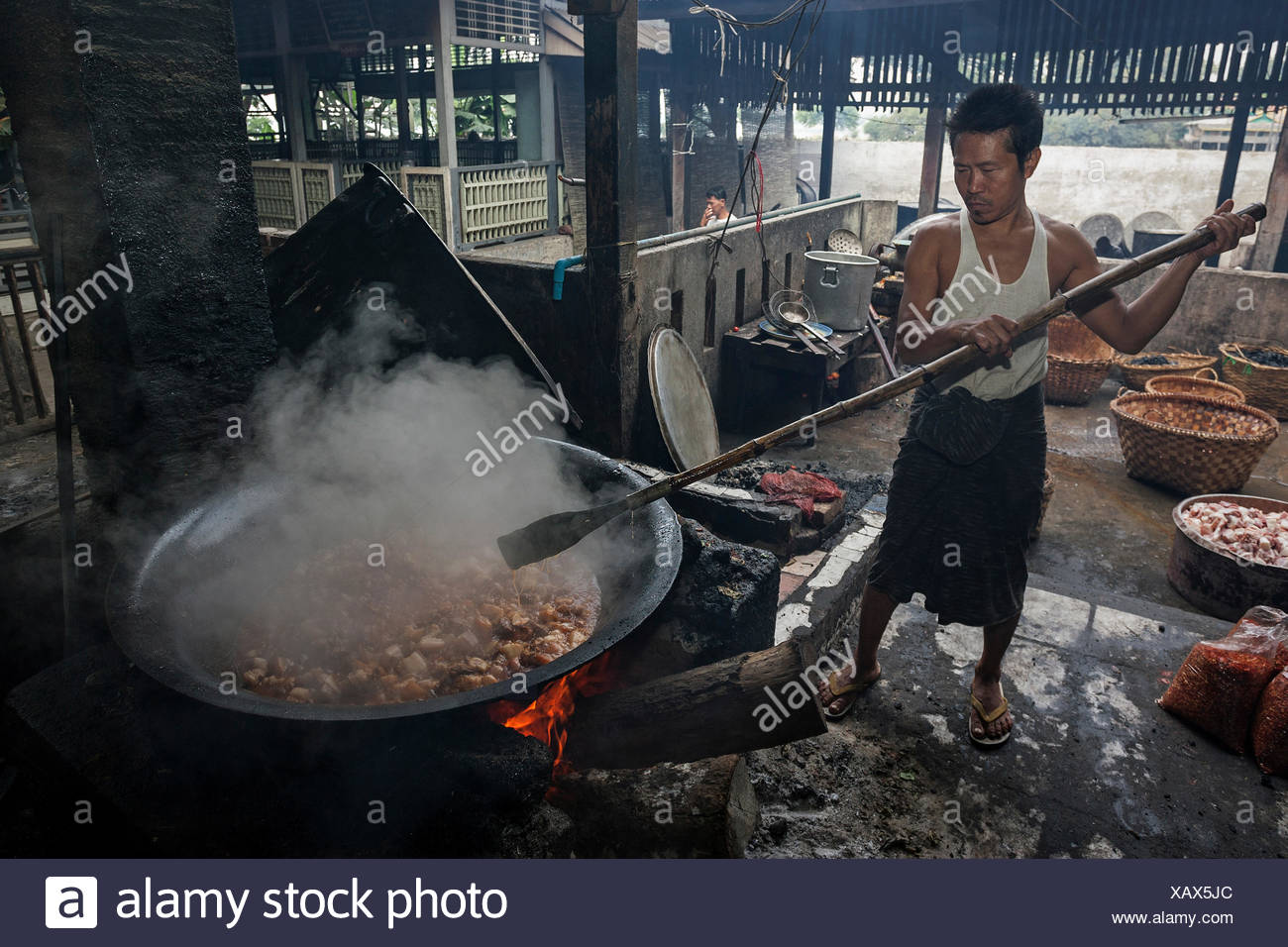 Cooking over an open fire, preparing food for the monks, catering in Mahagandayon Monastery, Amarapura, Divison Mandalay - Stock Image