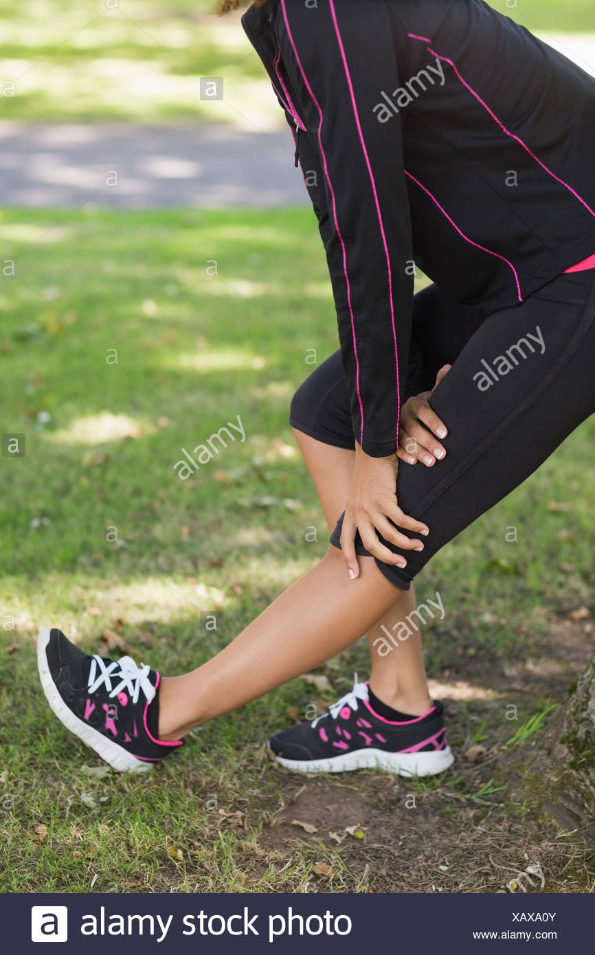 Mid section of woman stretching her leg during exercise at park Stock Photo